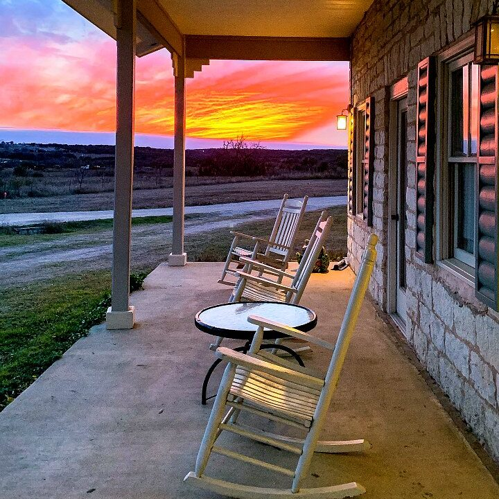 A porch with rocking chairs with a sunset in the background.