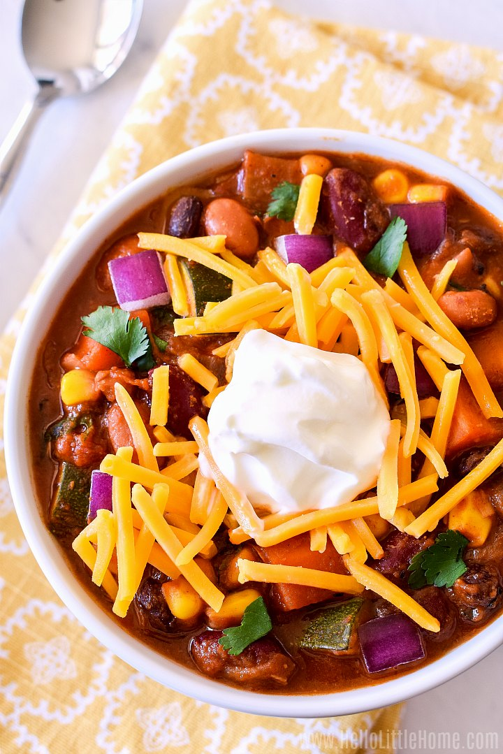 A overhead photo of a bowl of Vegetarian Bean Chili topped with shredded cheddar and sour cream.