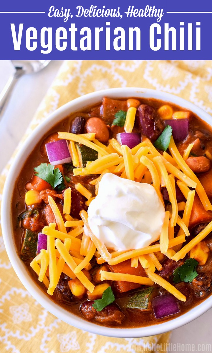 An overhead photo of a bowl of vegetarian chili topped with shredded cheese and sour cream.