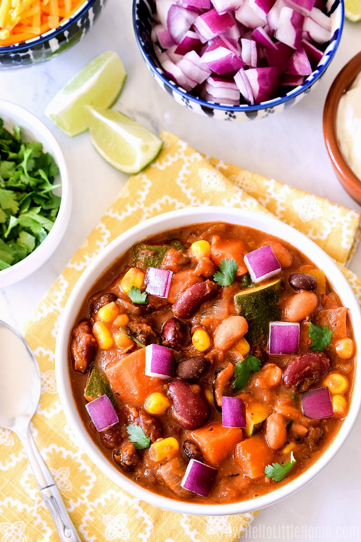 A bowl of veggie bean chili surrounded by small bowls of chili toppings.