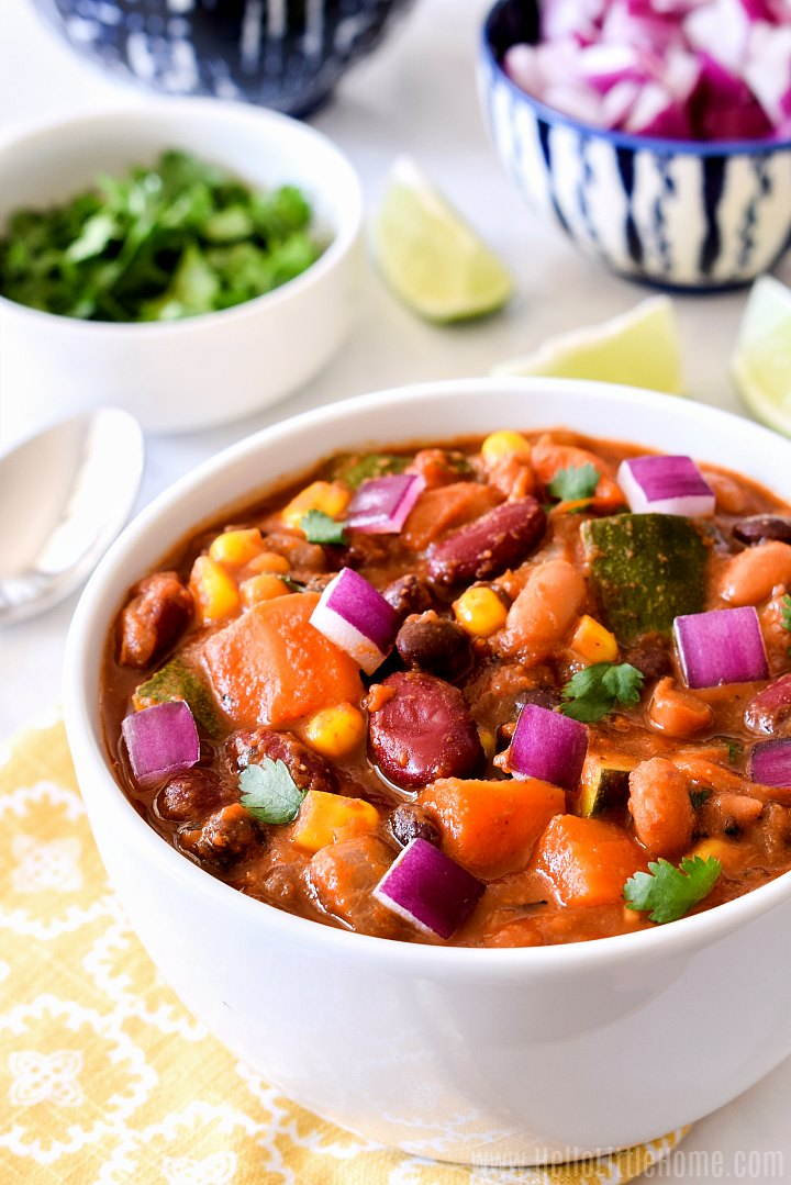 Veggie Chili served in a white bowl on a yellow patterned napkin with toppings in the background.