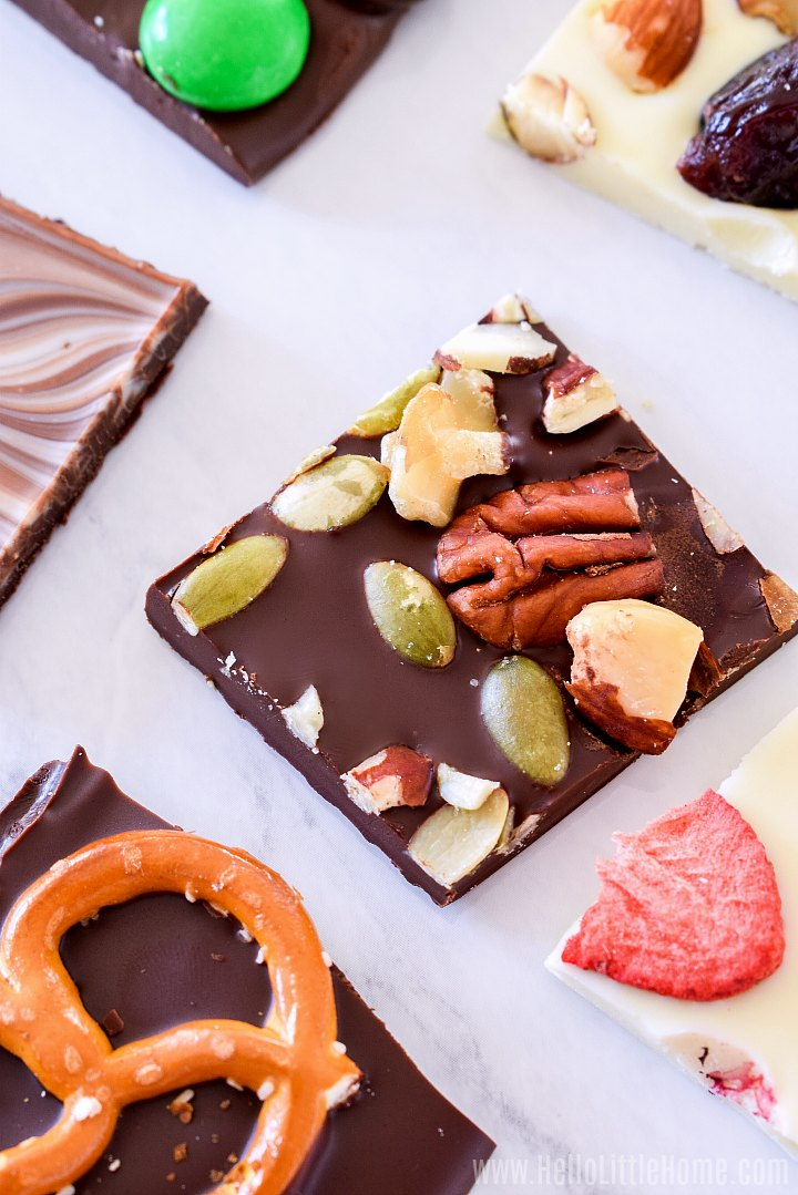 Different types of Chocolate Bark arranged on a white marble counter.