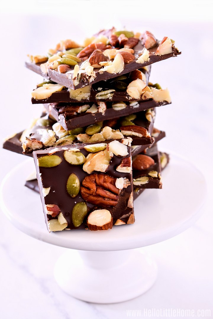 A small white pedestal topped with a stack of Chocolate Nut Bark.