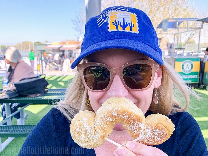 A woman holding a mustache shaped pretzel in front of her face.