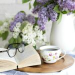 An open book topped with reading glasses next to a cup of coffee and flowers.
