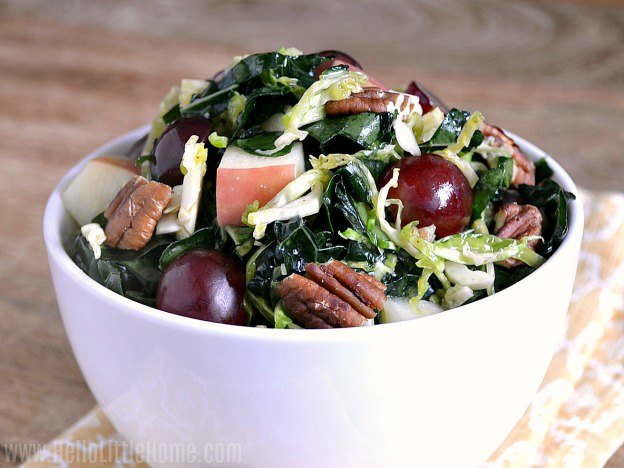 A white bowl filled with kale, apples, grapes, and pecans.