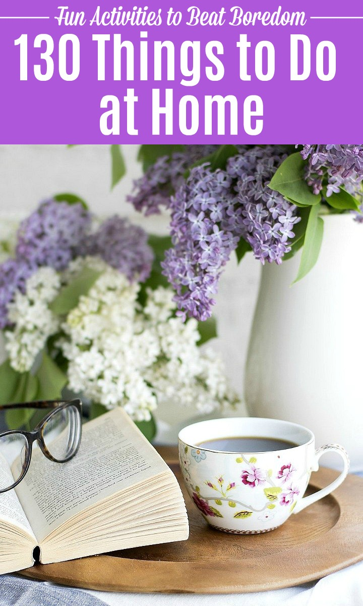 A book, pair of glasses, coffee, and flowers on a table.