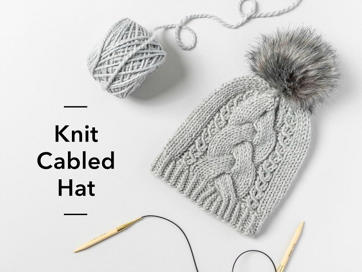 A cabled hat and knitting needles on a light grey table.