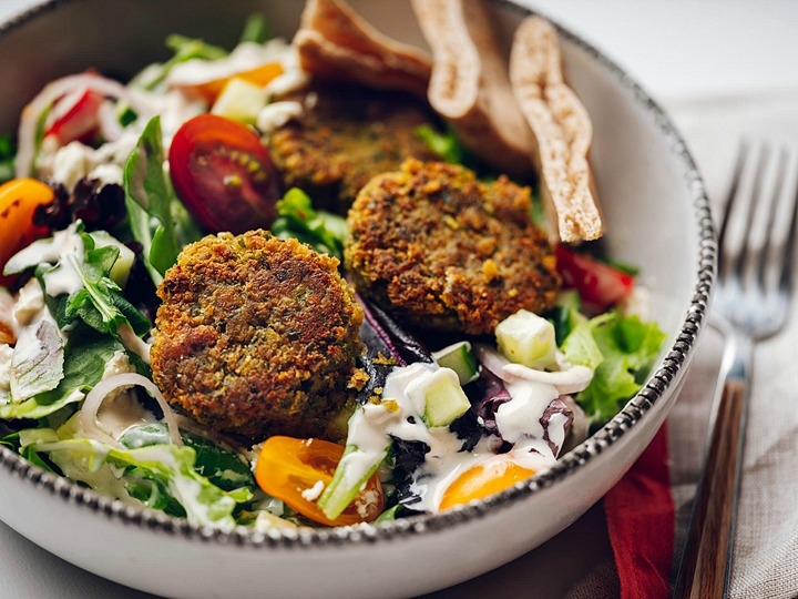 A bowl filled with salad, falafel, and pita bread.