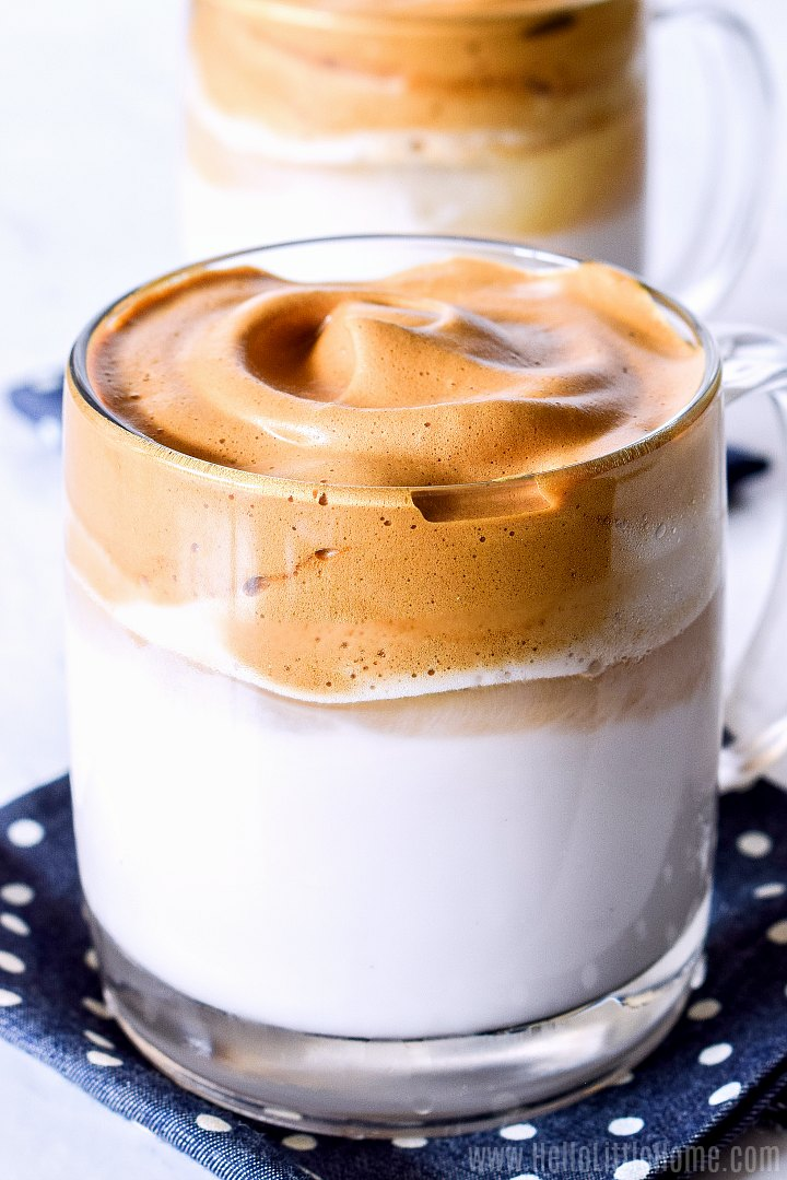 Closeup photo of milk topped with fluffy coffee in a glass mug.