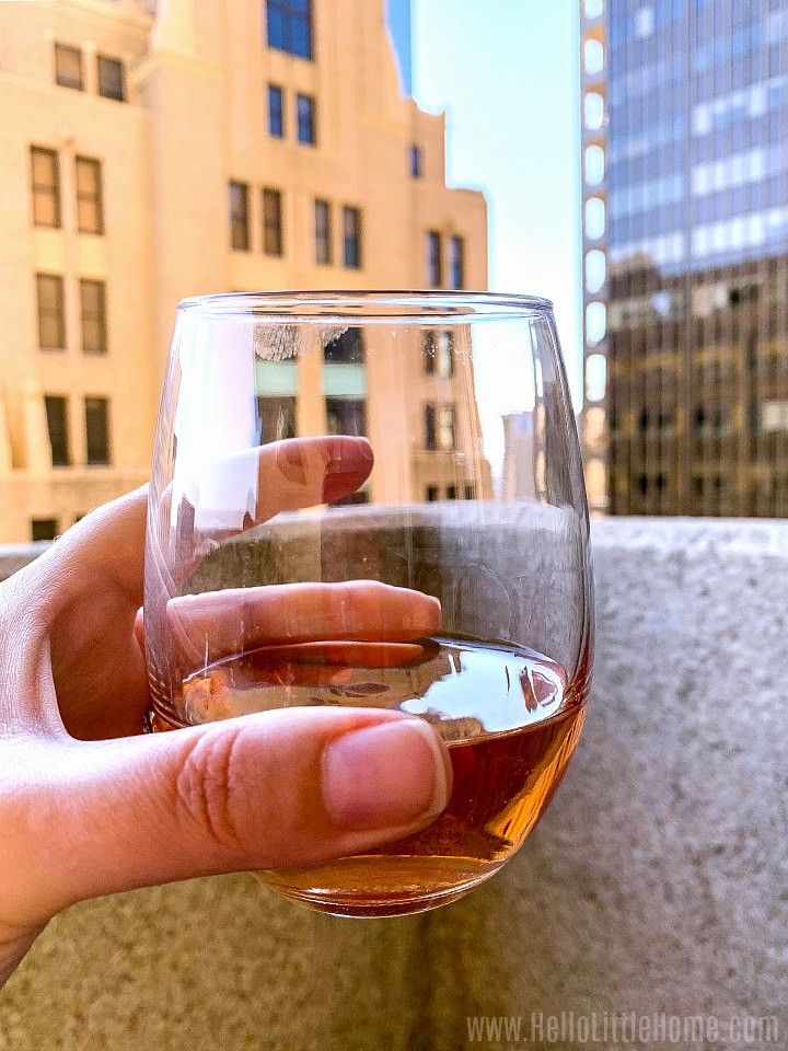 A hand holding a glass of rose with high rise buildings in the background.