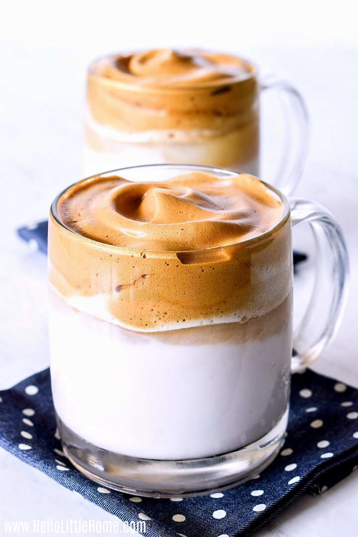 A whipped coffee with another behind it on a marble counter.