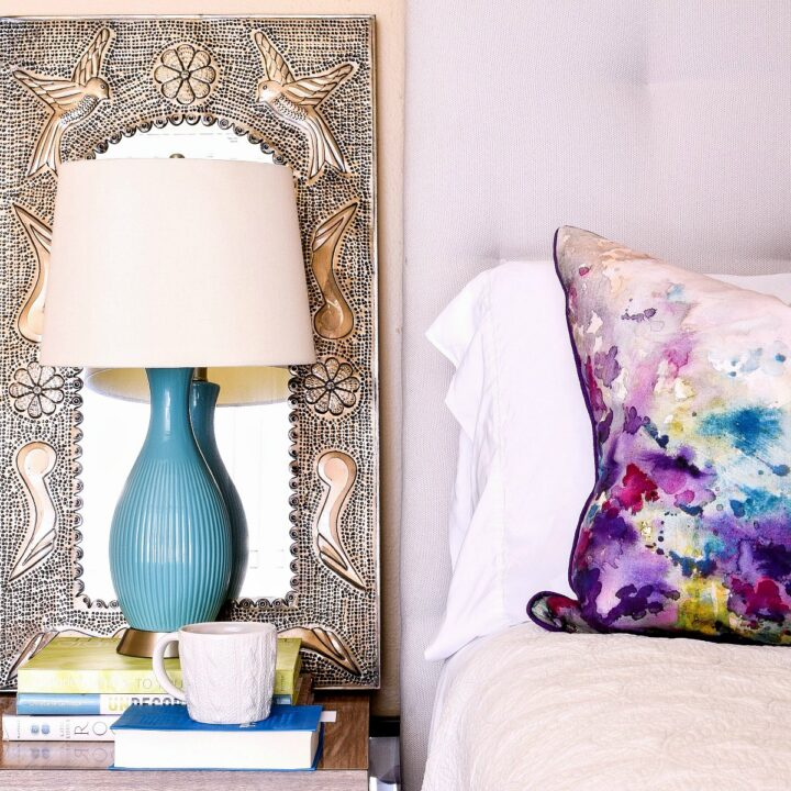 A bedside table with a lamp, books, and mug of tea.