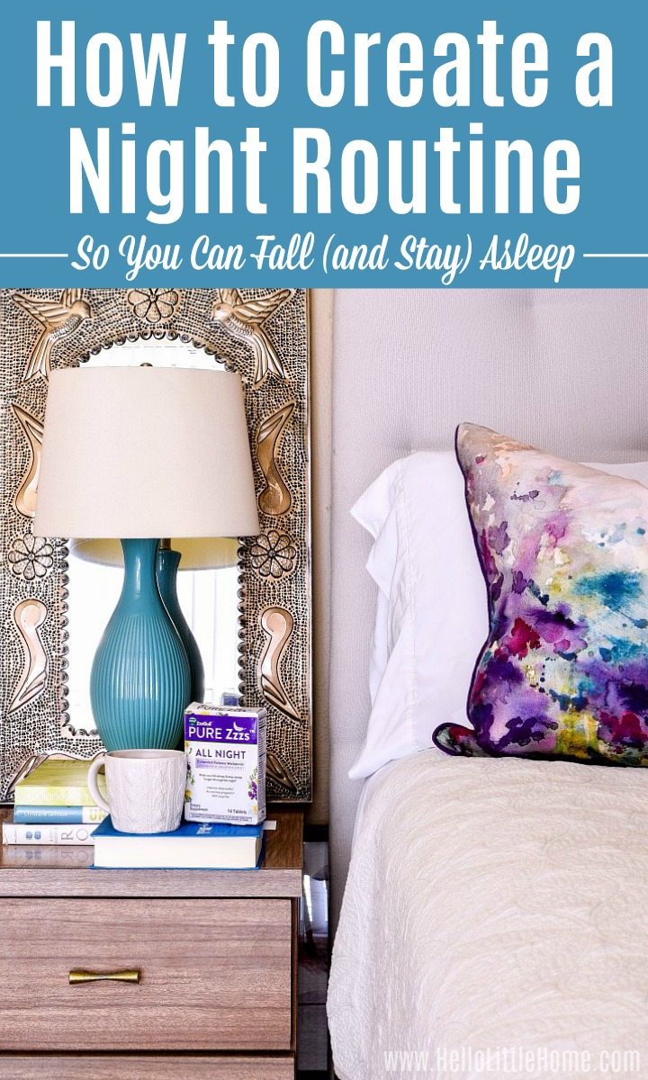 A beside table topped with books and a lamp next to a bed with colorful pillows.