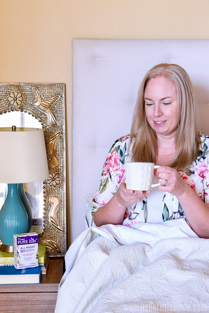 A woman sipping a mug of tea in bed.