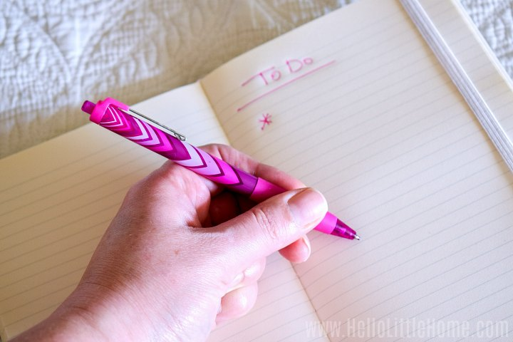 A hand writing a to do list in a journal.