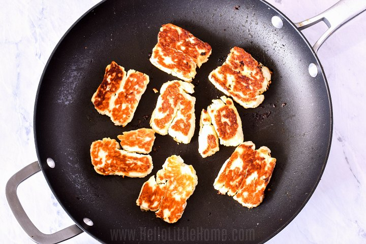 A frying pan with fried halloumi cheese in it.