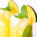 Closeup of tops of two mango mojitos garnished with mango and mint.