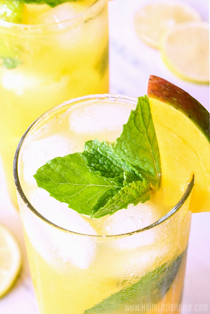 Closeup of a mango rum cocktail garnished with a mint sprig.