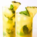 Two Pineapple Mojitos garnished with mint and fruit wedges.