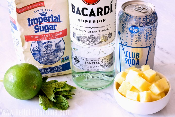 Pineapple Mojito ingredients arranged on a marble counter.