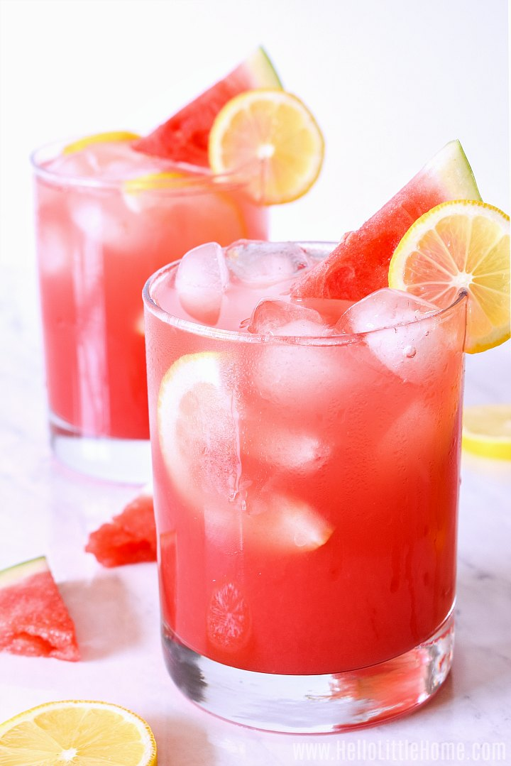 Glasses of the finished drink garnished with slices of lime and watermelon.