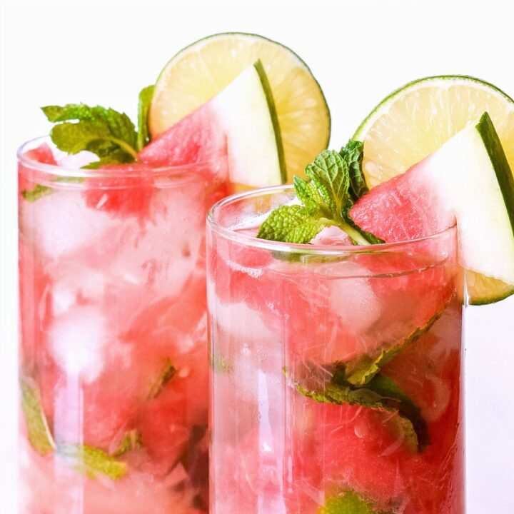 Watermelon Mojitos garnished with mini watermelon wedges, lime, and mint.
