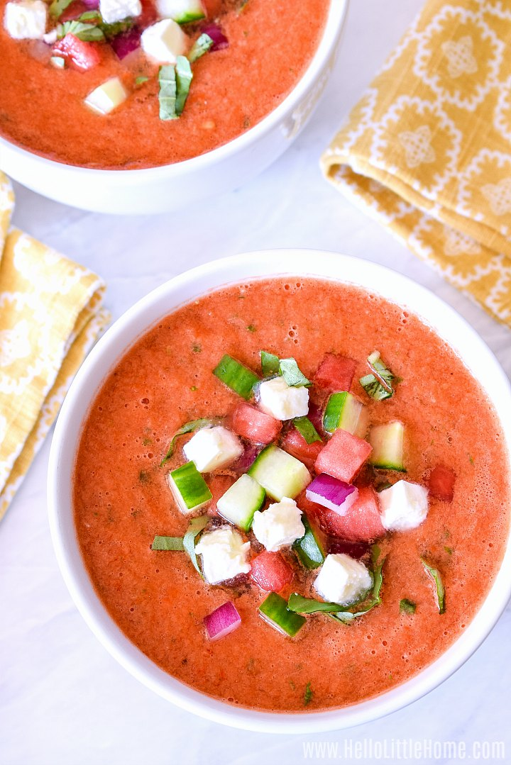 Bowls of soup topped with veggies and feta.