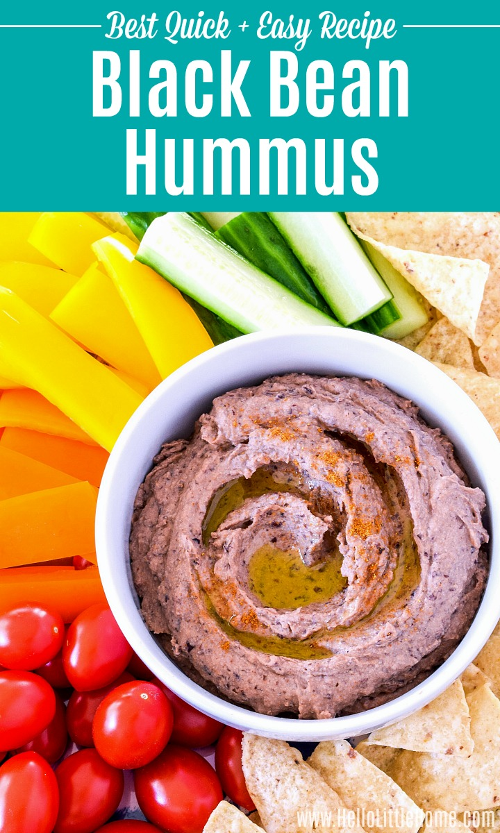 A bowl of black bean hummus on a tray of veggies and chips.