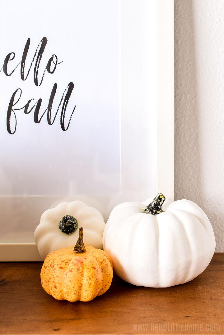 Three mini pumpkins on a wood table.
