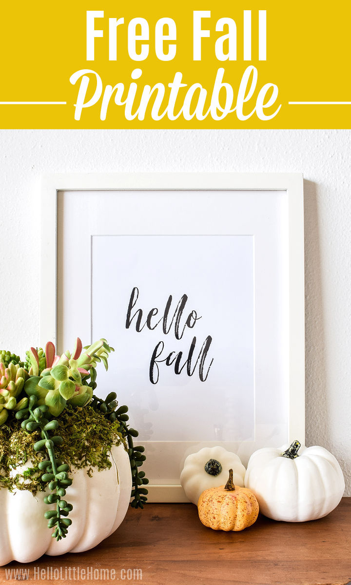 A Free Hello Fall Printable on a wood table with other autumn decor.