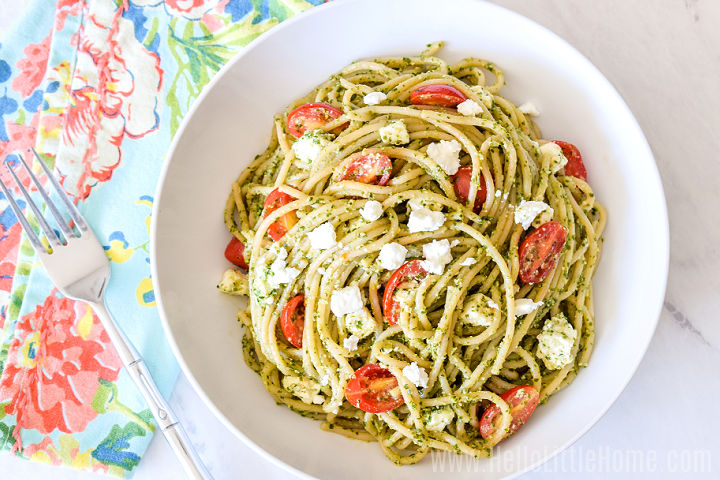 A bowl of kale pesto pasta, napkin, and fork on a marble counter.