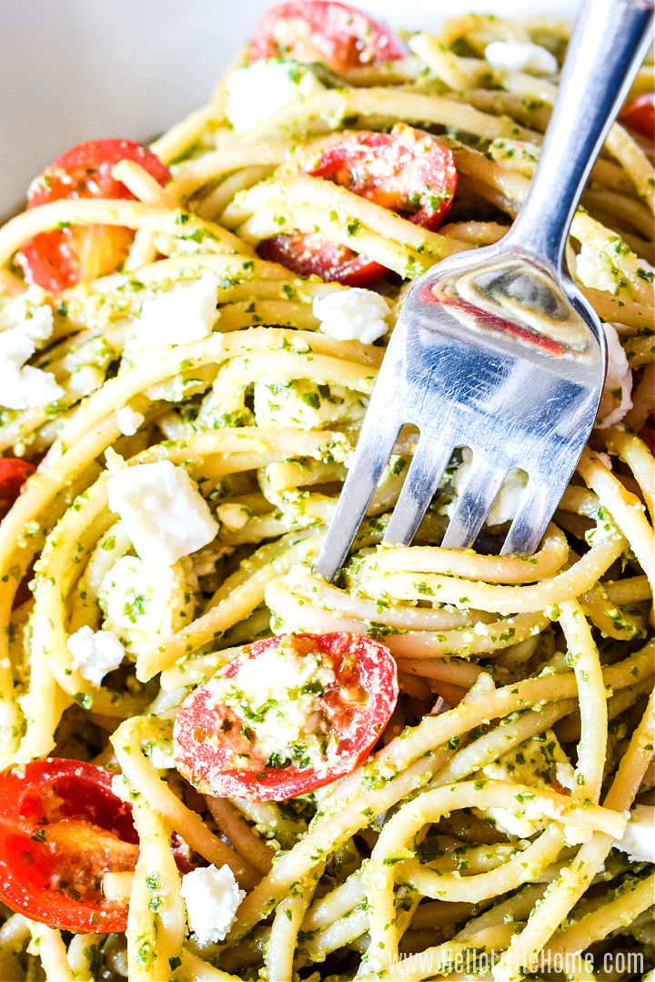 A fork twirling strands of kale tomato pasta.