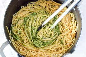 Mixing pesto with spaghetti in a big pot with tongs.