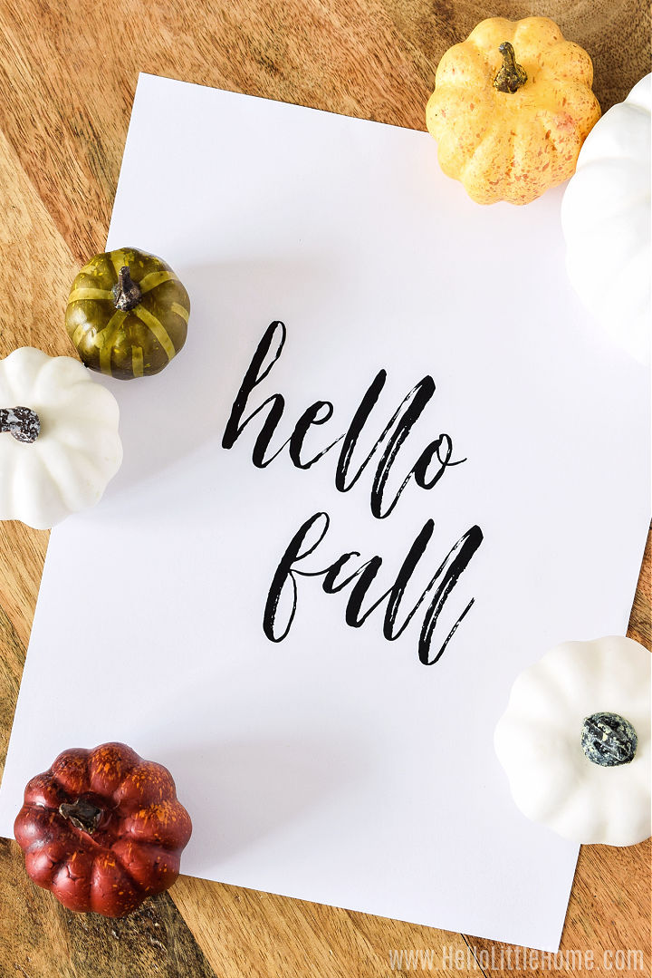 Printable on a wood table surrounded by mini pumpkins.