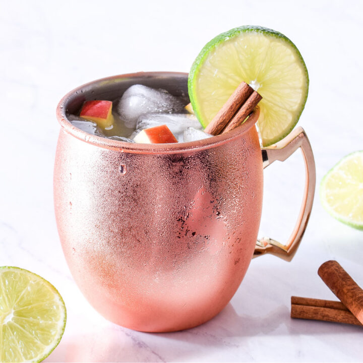 An Apple Cider Mule, cinnamon sticks, and lime slices on a counter.