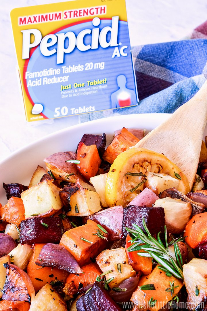 A spoon in a bowl of baked veggies with a box of Pepcid in the background.