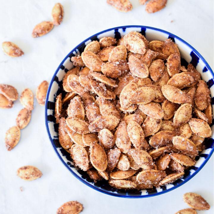 A overhead photo of a bowl of Cinnamon Sugar Pumpkin Seeds.