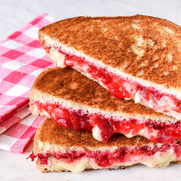 A stack of Cranberry and Brie Sandwiches next to a checked napkin.