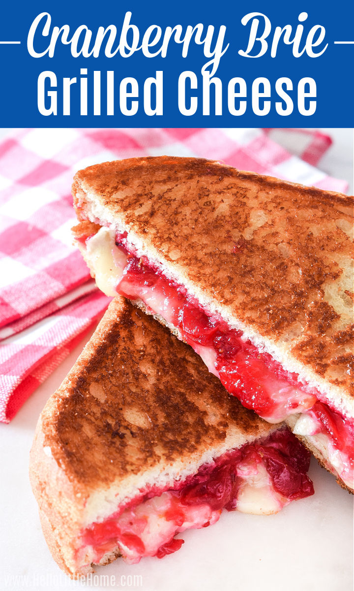Two Cranberry Brie Grilled Cheese halves stacked next to a check napkin.