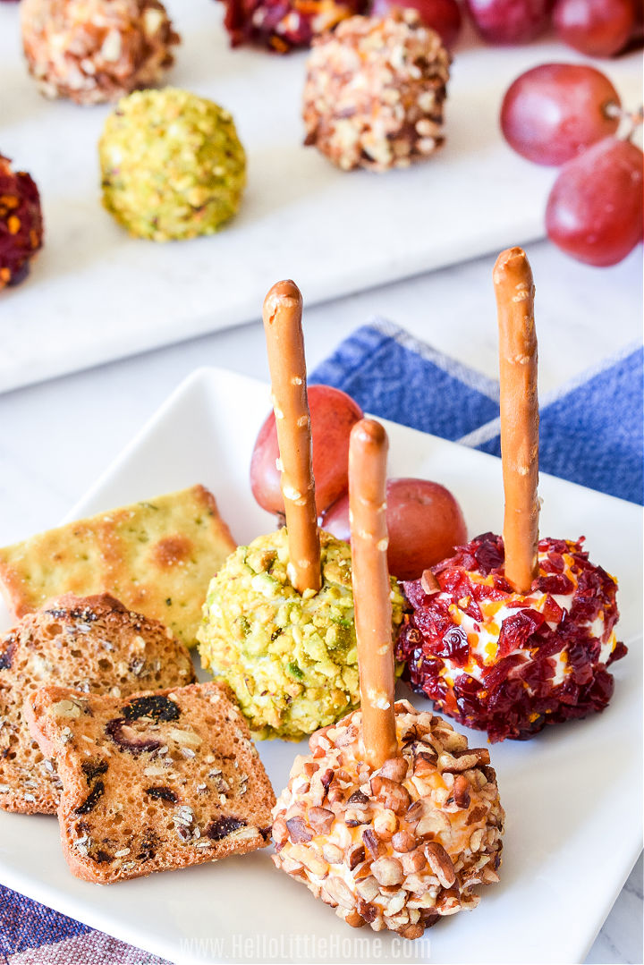 A small plate topped with mini cheese balls with pretzel sticks, crackers, and grapes.