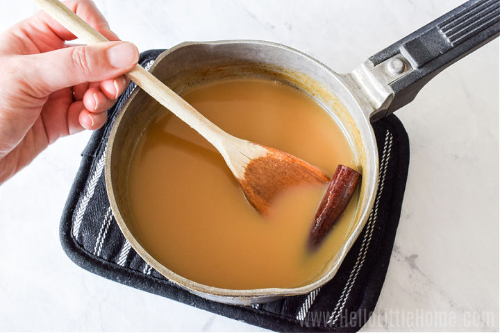 A hand stirring apple cider and a cinnamon stick in a saucepan.