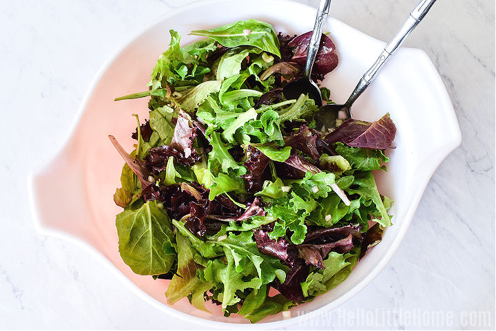 Mixing the greens and vinaigrette in a large bowl with two spoons.