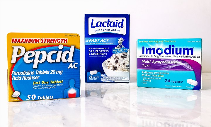 Boxes of Pepcid, Lactaid, and Imodium on a marble counter.