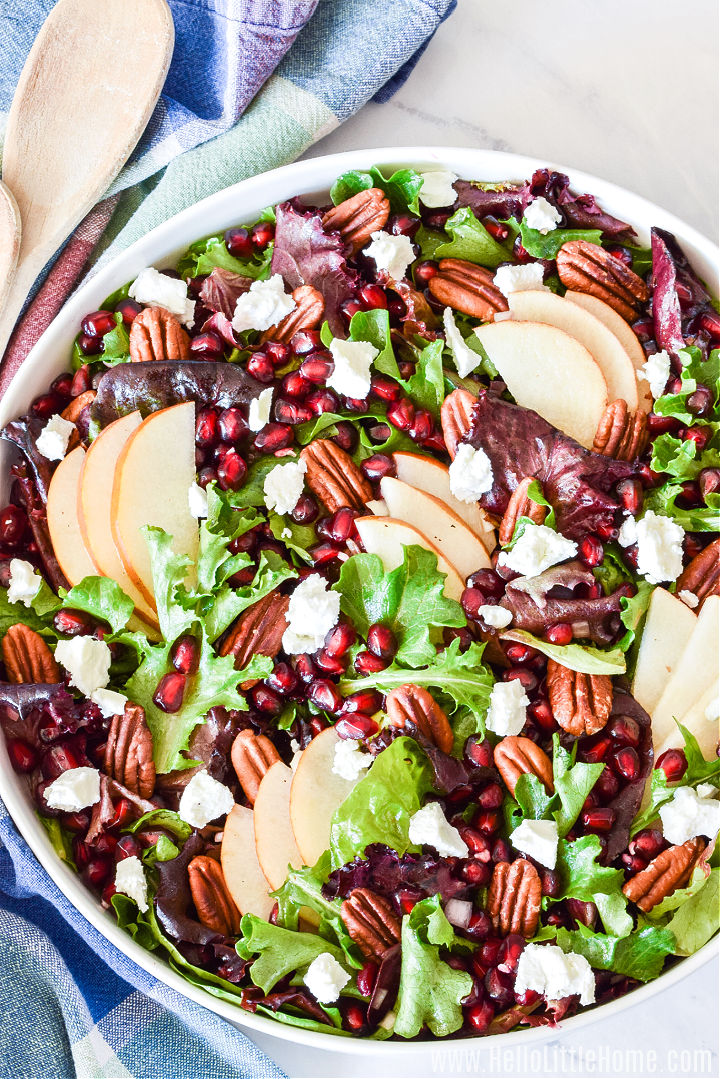 A platter topped with the finished pomegranate, pear, and goat cheese salad.