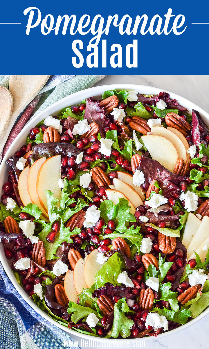 The finished Pomegranate Salad served on a round platter with two wood spoons.