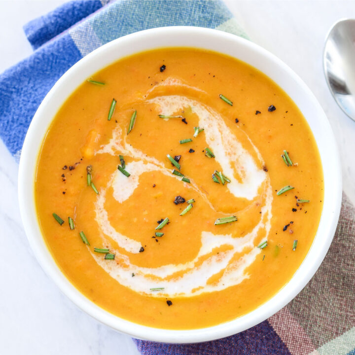 A bowl of Roasted Pumpkin Soup on a napkin and next to a spoon.
