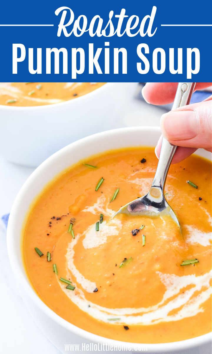 A hand holding a spoon in a bowl of Roasted Pumpkin Soup.