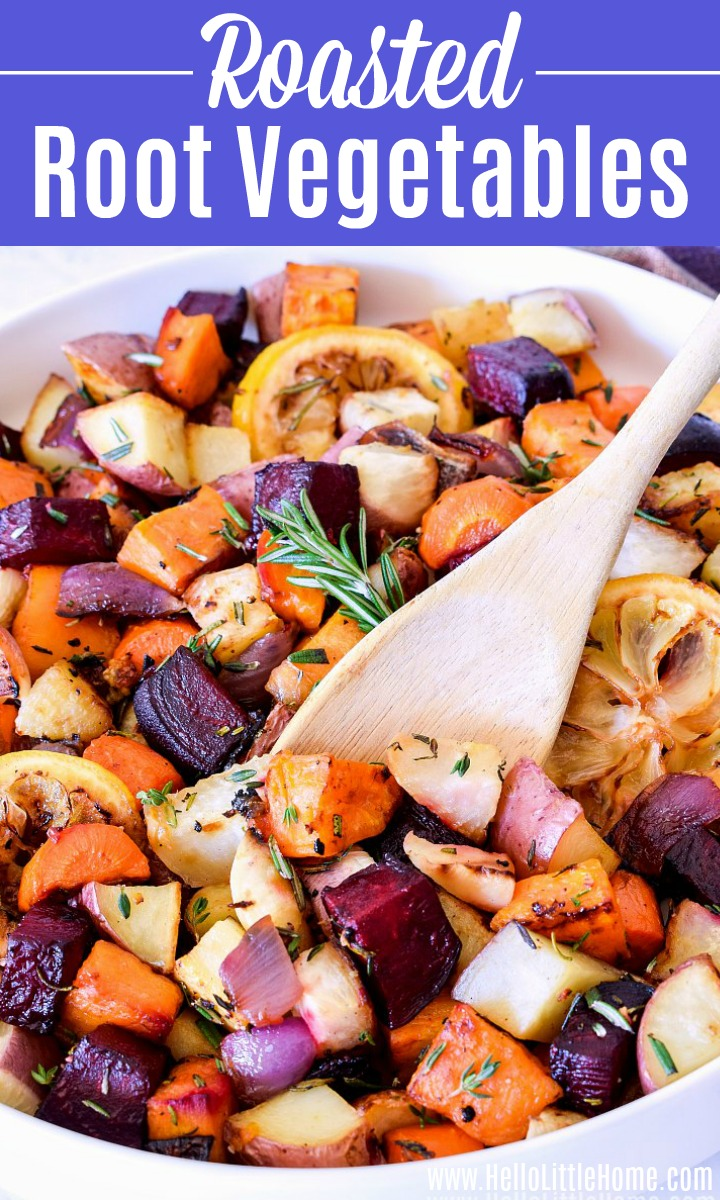 A wood spoon stirring a platter of Roasted Root Vegetables.