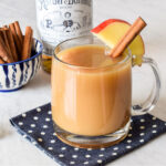 A mug of Spiked Apple Cider next to a bowl of cinnamon sticks and bottle of rum.